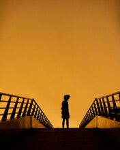 Silhouette Man Standing By Railing Against Orange Sky