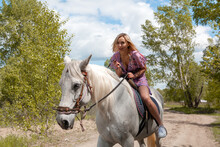 Beautiful Young Woman Riding Free White Horse In Forest On Summer Warm Day. Outdoor Photography