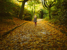 Full Length Of Young Girl Walking On Footpath During Autumn