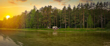 Camper Stands Near The Forest And Lake.