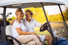 Elderly Golf Couple Rides In A Golf Cart.