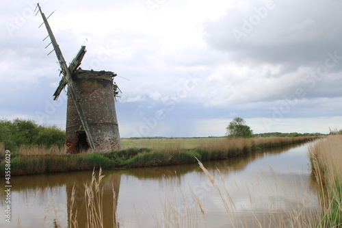 Landscape of ancient brick windmill mill pump with wood sails reflect in river w Fototapet
