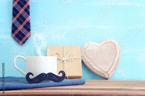 image of fathers day composition with hot cup of coffee over table and blue background