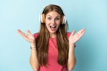 Young Caucasian Woman Isolated On Blue Background Surprised And Listening Music