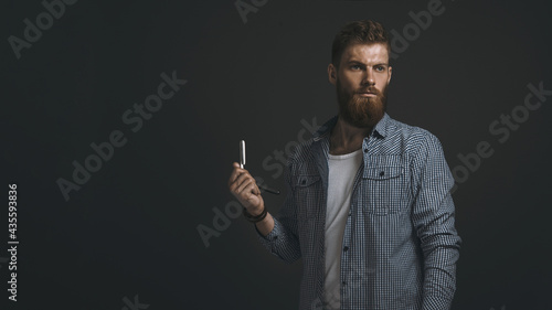 Fotografia Portrait of brutal bearded man with straight razor in his hand