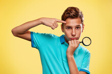 A Teenage Boy In A Blue T-shirt With Pimples Pointing On His Face, Holding A Magnifying Glass. Yellow Background. Cosmetology, Dermatology And Acne Concept