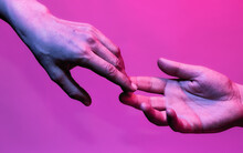 Hands Of Man And Woman At The Time Of Separation In Neon Light. Concept Of Breakup Between Two People.