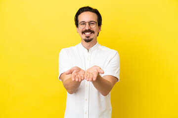 Young caucasian man isolated on yellow background holding copyspace imaginary on the palm to insert an ad