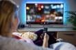 Leinwandbild Motiv Woman relaxing at home in evening and watching TV
