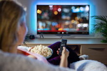 Woman Relaxing At Home In Evening And Watching TV