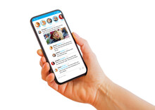 Person Holding Mobile Phone In Hand With Sample Social Media Microblogging App On The Screen