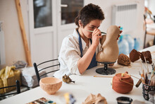 Accurate Pottery Shop Employee Shaping Statue Face With Modeling Knife