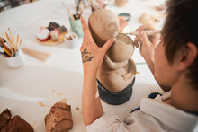 Pottery Artist In Process Of Carving Animal Statuette Face