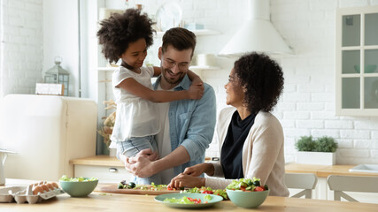 Smiling young multiracial mom and dad cook healthy delicious vegetarian salad with ethnic small daughter. Happy multiethnic family with girl child have fun prepare food in kitchen. Adoption concept.