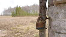 An Old Rusty Padlock On The Side Of The Wall From The Ruined And Abandoned House