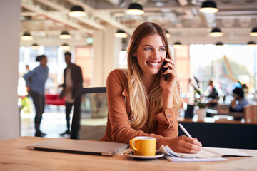 Young Businesswoman Sitting At Desk On Phone Call In Modern Open Plan Office