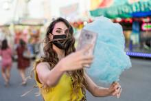 Chica Joven Con Mascarilla Por Covid 19 Tomando Un Algodón De Azucar Azul Y Tomando Selfies Con El Movil En Una Zona De Atracciones De Una Feria