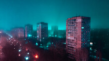 Neon Lighted Urban Aerial Panorama In A Bad Ghetto District. Deep Blue Colored Light Just From The Dark On The Horizon