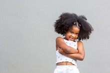 The Curly-haired African American Girl Stood Happily Smiling And Folded Her Arms.