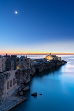 Old Buildings And Church Of Vieste Lit By Moon At Dusk, Vieste, Foggia Province, Gargano National Park, Apulia, Italy