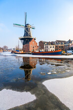 Windmill De Adriaan Reflected In The Canal Of Icy River Spaarne, Haarlem, Amsterdam District, North Holland, The Netherlands