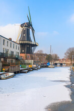 Windmill De Adriaan Along The Frozen Canal Of Spaarne River, Haarlem, Amsterdam District, North Holland, The Netherlands