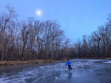 Man Skates The Frozen C And O Canal (Chesapeake And Ohio Canal) Under A Hazy Full Moon, Potomac, Maryland