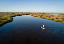 Stand Up Paddle Boarder Paddles Through A Chesapeake Bay Salt Marsh Near Hampton, Virginia