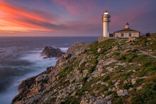 Sea Landscape View Of Cape Tourinan Lighthouse At Sunset With Pink Clouds, Galicia