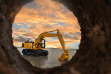 Crawler Excavator Are Digging Soil In The Tunnel Construction Site. With A Sky After Sunset Background