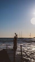 Silueta De Mujer En Un Puente De Madera Al Atardecer En El Mar