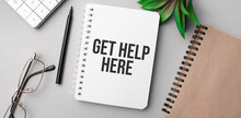 Get Help Here Is Written In A White Notebook With Calculator, Craft Colored Notepad, Plant, Black Marker And Glasses.