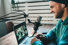 Handsome Content Creator Streaming His Live Podcast Using Professional Microphone At His Broadcast Studio