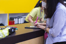 Asian Woman Signing Transaction Receipt With At Cashier Counter.