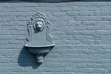 Old Lion's Head Fountain Mounted On A Brick Wall Coated With A Layer Of Blue Paint