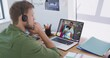 Caucasian man wearing phone headset having a video call with male colleague on laptop at office