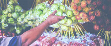 People Buying Guava At A Market Stall In Bali, Indonesia. Fruits And Vegetables At A Farmers Market. Organic Fresh Agricultural Product At Farmer Market.