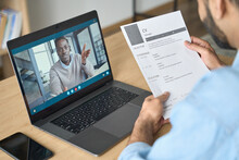 Young Indian Confident Businessman Holding Cv Talking To Male Black Man Potential Employee Hiring For Job. Virtual Video Call Between Employer And Manager Worker. Remote Recruitment Work Concept.