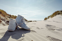Against Sunshine View On Pair Of White Ankle Sneakers Laying On Sand Dune. North Sea Coastal Landscape.