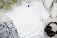 White Womens Cotton Tshirt Mockup With Flowers, Jeans, Sneakers And Black Headphones On Wooden Background. Design T Shirt Template, Print Presentation Mock Up. Top View Flat Lay.