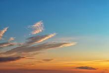 Calm Golden Blue Sunset Sky With Few Long Clouds At Left. The Rays Of The Setting Sun Gilded The Clouds And The Sky Above The Horizon. Summer Evening Sky At Golden Hour. Weather Forecast