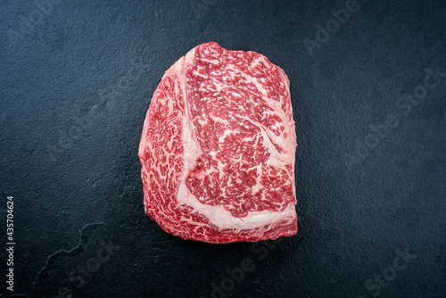 Raw dry aged wagyu cutlet steak cut offered as top view on black background with copy space