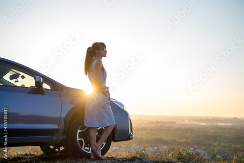 Fotografering Happy young woman driver in blue dress leaning on her car enjoying warm summer day