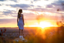 A Young Woman In Summer Dress Standing Outdoors Enjoying View Of Bright Yellow Sunset.