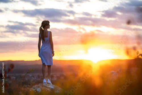 A young woman in summer dress standing outdoors enjoying view of bright yellow sunset Fototapet