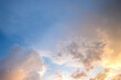 canvas print picture - Dramatic sunset sky landscape with puffy clouds lit by orange setting sun and blue heavens.