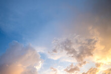Dramatic Sunset Sky Landscape With Puffy Clouds Lit By Orange Setting Sun And Blue Heavens.