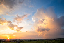 Dramatic Sunset Landscape Of Rural Area With Stormy Puffy Clouds Lit By Orange Setting Sun And Blue Sky.