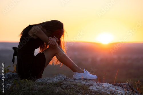 Canvastavla Young depressed woman in black short summer dress sitting on a rock thinking outdoors at sunset