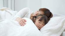 ベッドに横たわる娘を見守る母